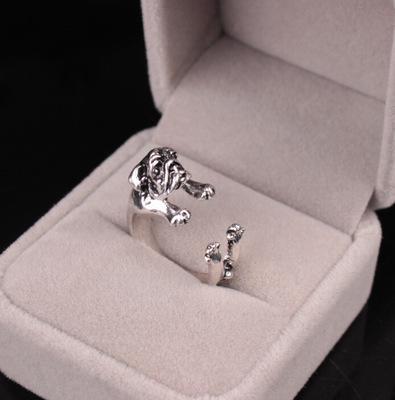 SIlver ring med hund som kramar fingret