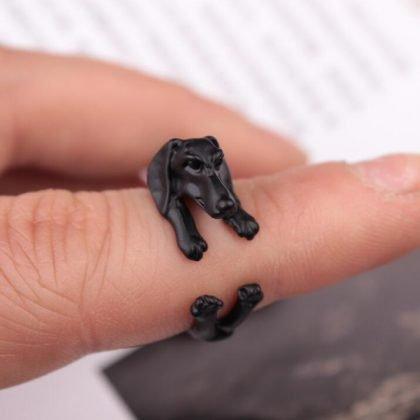 Svart ring med hund som kramar fingret