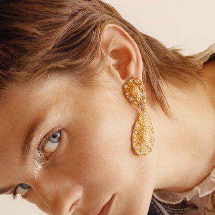 Örhänge i guld omgivna med strass