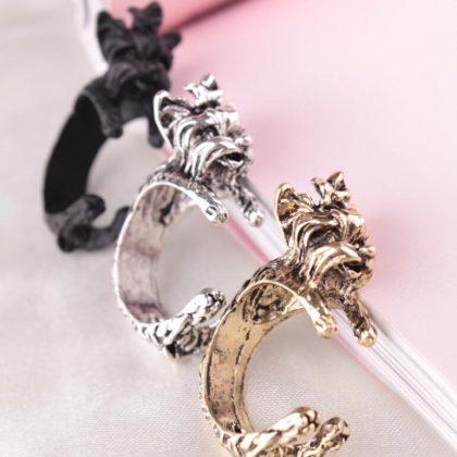 Ring med terrier hund som kramar fingret guld, silver och svart