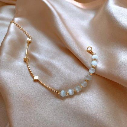 Armband med vita opalstenar och guldpläterade hjärtan